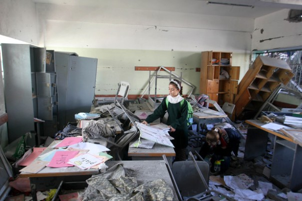 A Palestinian school girl inspects the damage in a destroyed classroom